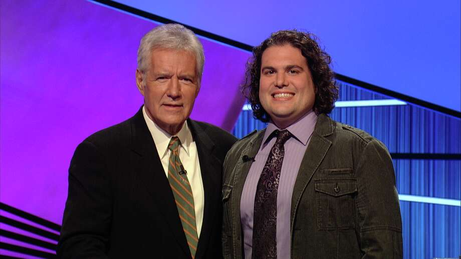 "Joshua Bartlett, a 32-year-old graduate student from Albany, poses with ""Jeopardy!"" host Alex Trebek. Bartlett is slated to appear on the show Thanksgiving night. (Jeopardy Productions, Inc.)"