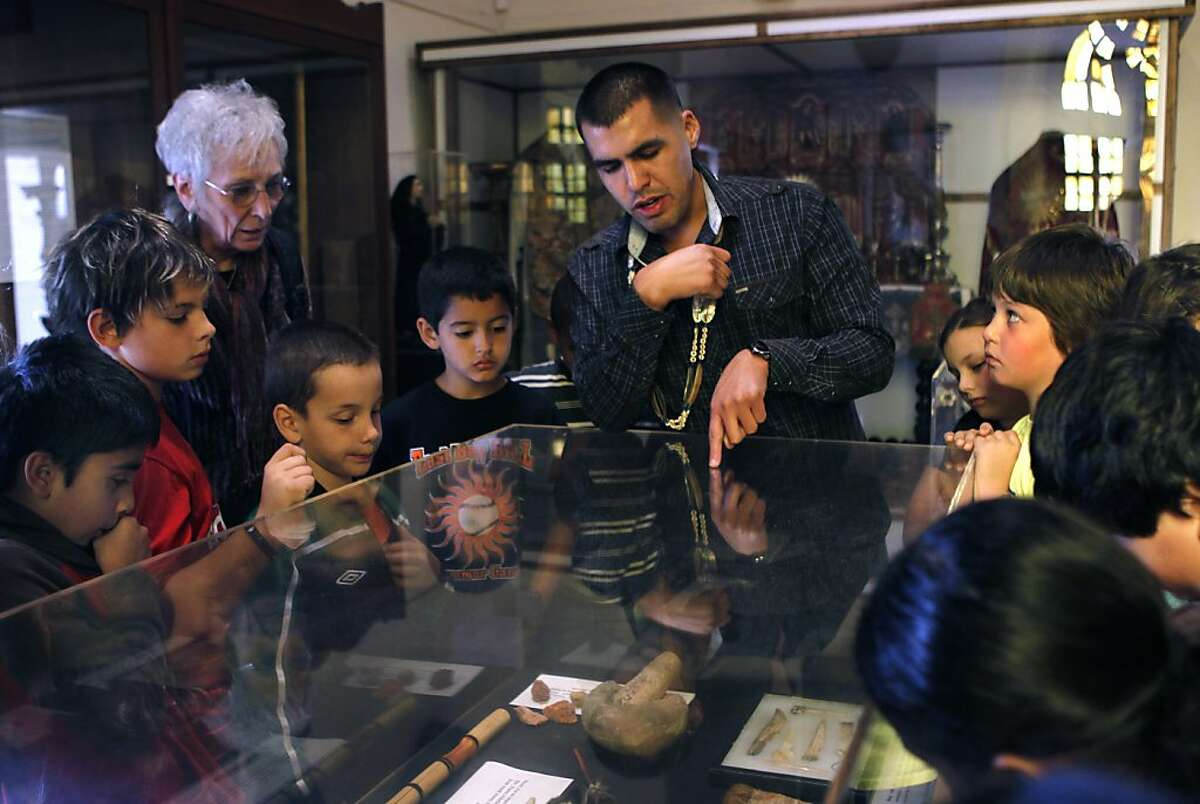 Vincent Medina describes Ohlone artifacts displayed at Mission Dolores for students visiting from Oakland's Hillcrest Elementary School in San Francisco, Calif. on Thursday, Nov. 15, 2012. Medina is hoping to revive the Cochoenyo language that was spoken by his Ohlone ancestors.