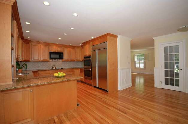 The kitchen, joined to the rest of the rooms by hardwood flooring, features an eat-in area, granite counters and sliding doors that lead to a large wood deck in the backyard. Photo: Contributed Photo