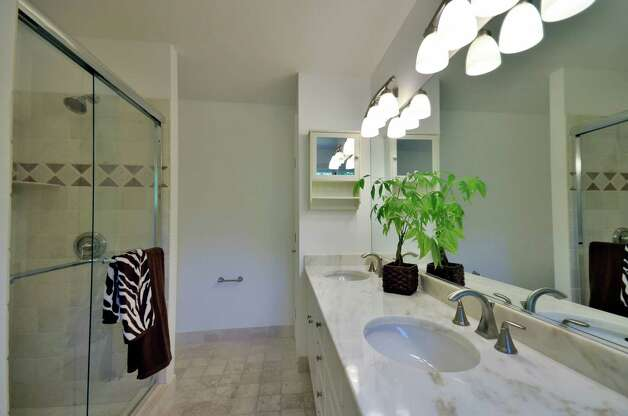 The master bath has a tile floor, a Hydro jetted tub, walk-in shower stall and white subway tile backsplash. Photo: Contributed Photo