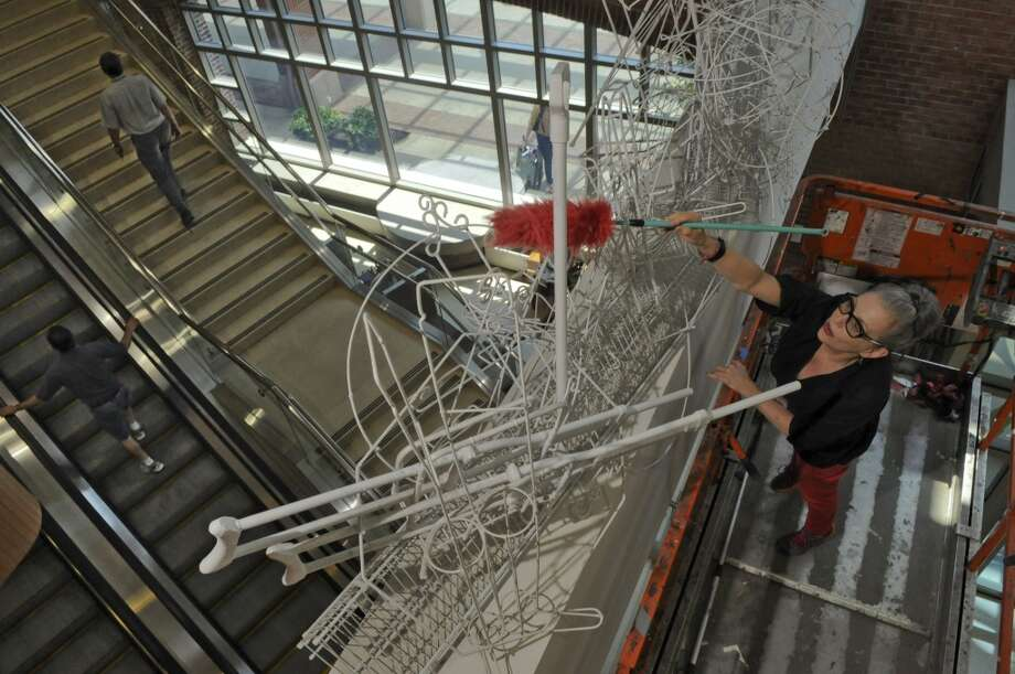 "Albany International Airport Art & Culture Program Director Sharon Bates dusts artist Edward Mayer's ""What Comes Around: Lines of Types, What Goes Around: Types of Lines,"" at the airport's passenger terminal  on Wednesday June 20, 2012 in Colonie, NY. (Philip Kamrass / Times Union) (Albany Times Union)"