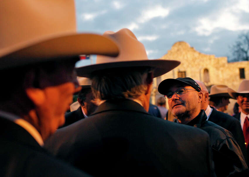 Singer and Alamo collector Phil Collins, right, talks with members of the Sons of the Republic of Texas after the Dawn at the Alamo ceremony in San Antonio, Texas on Friday, March 6, 2009. The annual ceremony honors the 200 fallen Alamo defenders and nearly 600 Mexican troops killed or wounded in the battle of the Alamo. (AP Photo/San Antonio Express-News, Lisa Krantz)