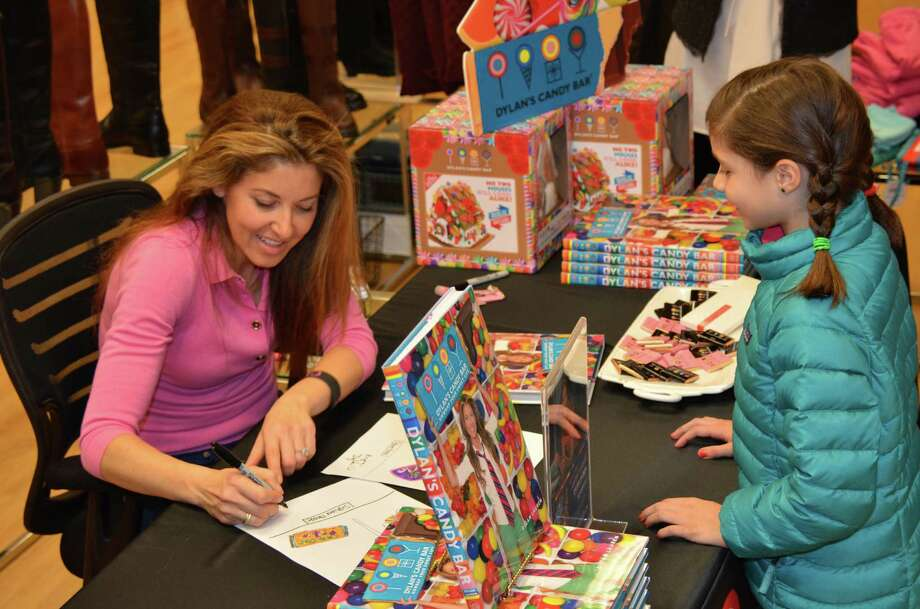 Dylan Lauren, owner of Dylan's Candy Bar, signs a book for 8-year-old Claire Galper at the Darien Sport Shop Tuesday, Nov. 20, 2012. Photo by Jeanna Petersen Shepard Photo: Freelance Photo