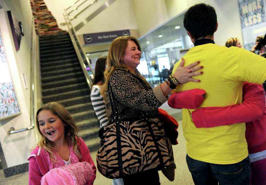 Larry Snyder of Cooperstown greets his returning family on Wednesday, Nov. 21, 2012, at Albany International Airport in Colonie, N.Y. They are, from left, Jayne Snyder, 8; Jackie Snyder, and Helen Snyder, 10. (Michael P. Farrell/Times Union) Photo: Michael P. Farrell
