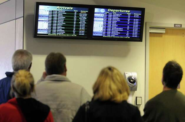 People waiting for holiday travelers to land look at the  arrivals board at Albany International Airport Colonie, N.Y Wednesday Nov. 21, 2012. (Michael P. Farrell/Times Union) Photo: Michael P. Farrell