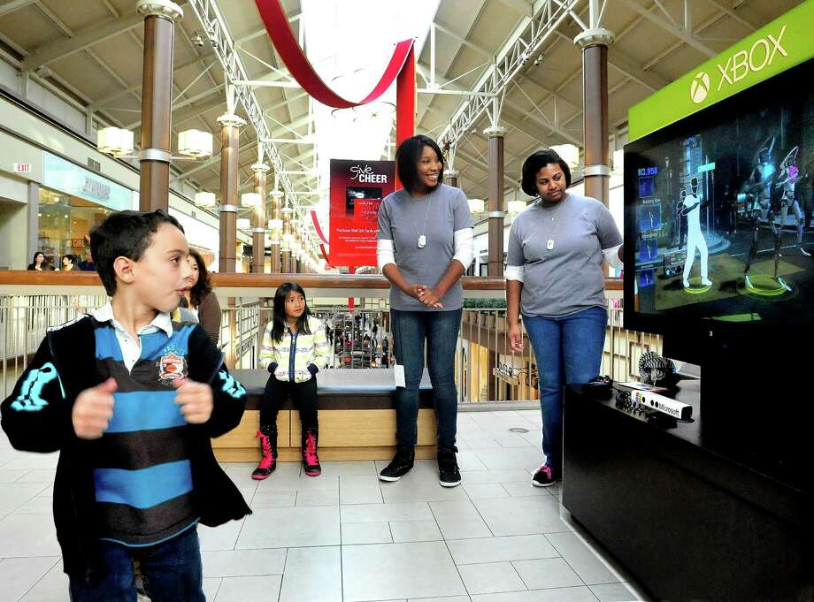 Niko Minigiello, 7, of Ridgefield, left, moves to the Dance Central 3 Xbox with Kinect at the Danbury Fair mall Sunday, Nov. 18, 2012. Microsoft demonstrators Teresa Johnson, center, and Janelly Sanchez, right, watch the screen. Photo: Michael Duffy / The News-Times