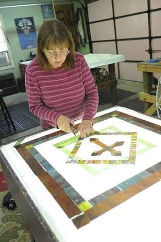 Lynn Metz displays a piece of stained glass nearing completion at Beaumont Leaded Glass Studio on Thursday. Guiseppe Barranco/The Enterprise