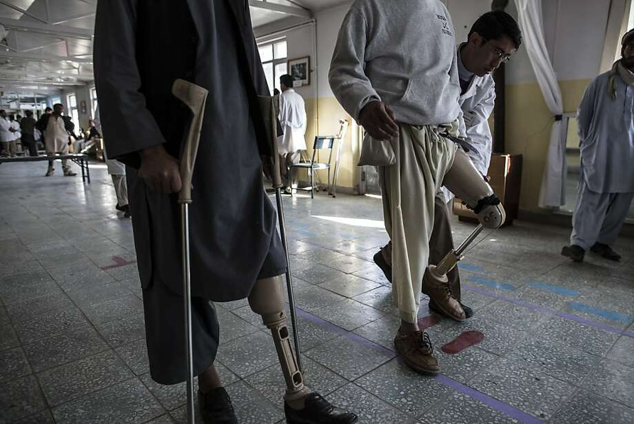 An orthopedic specialist checks the mobility of new prosthetic limb being fitted on to a patient at the International Committee of the Red Cross (ICRC), orthopedic center on November 20, 2012 in Kabul, Afghanistan. Photo: Daniel Berehulak, Getty Images