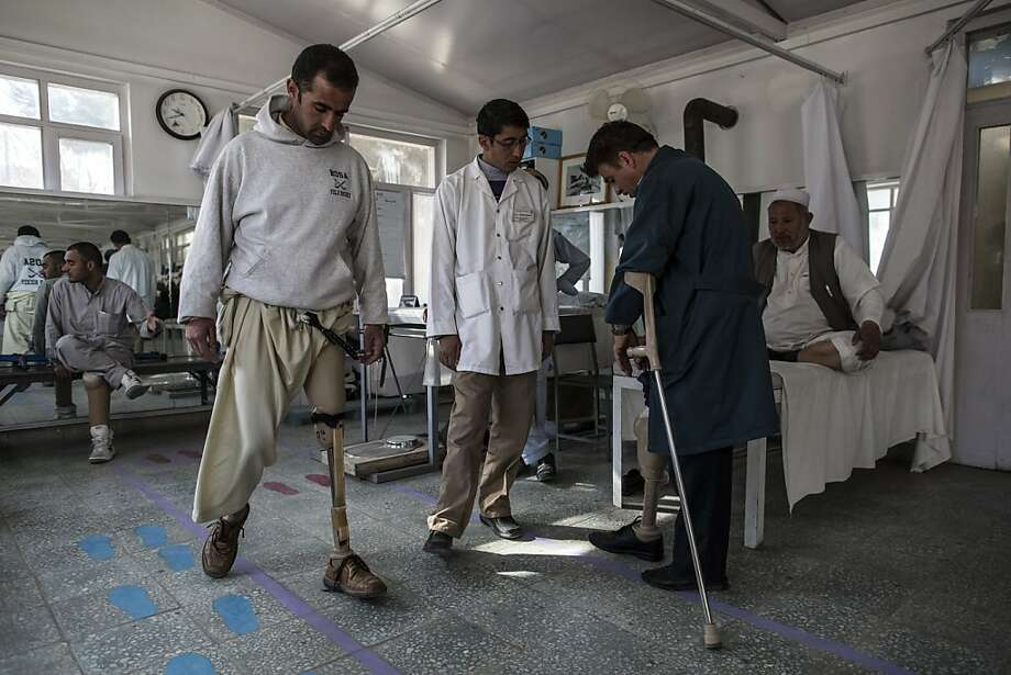 Hassibullah, 30, (left) who lost his after stepping on a mine, practices walking with his new prosthetic leg at the International Committee of the Red Cross (ICRC), orthopedic center on November 20, 2012 in Kabul, Afghanistan. Photo: Daniel Berehulak, Getty Images