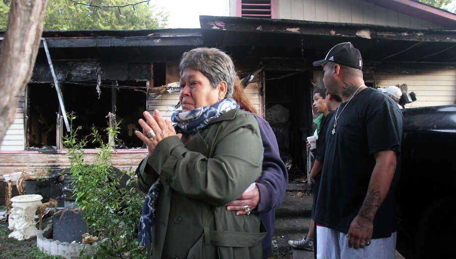 Homeowner Graciela Galvan cries after her house in the 6500 block of Marcum Drive burned. The fire began about 4:15 a.m. Wednesday and was believed to have been caused by malfunctioning wiring. Firefighters deemed the structure a total loss. Photo: JOHN DAVENPORT, San Antonio Express-News / ©San Antonio Express-News/Photo Can Be Sold to the Public