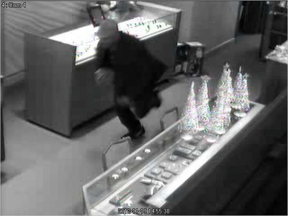 Still photos from the larceny at Reid's Jewelers on the afternoon of Nov. 19, 2012. Suspect was last seen running west on Cherry Street toward Park Street in New Canaan, CT. The suspect made off with a $30,000 Rolex watch. Photo: Contributed