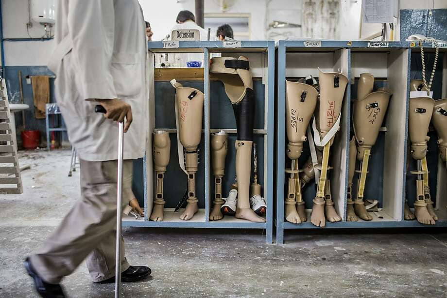 An orthopedic technician walks past prosthetic limbs being stored for patients at the International Committee of the Red Cross (ICRC), orthopedic center on November 20, 2012 in Kabul, Afghanistan. Photo: Daniel Berehulak, Getty Images