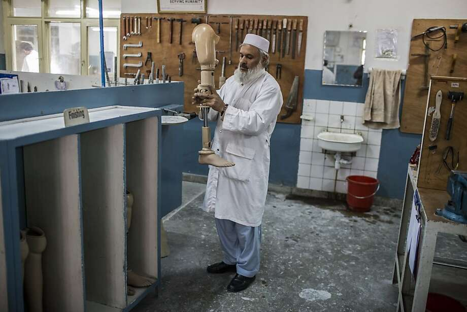 An orthopedic technician observes the mechanics of a prosthetic limb at the International Committee of the Red Cross (ICRC), orthopedic center on November 20, 2012 in Kabul, Afghanistan. Photo: Daniel Berehulak, Getty Images