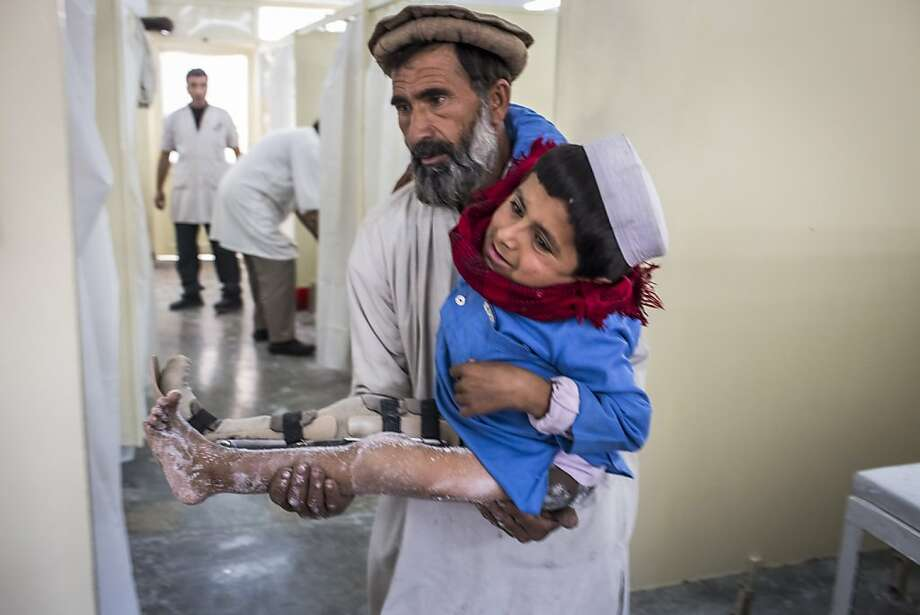 Bismillah Gul, 12, suffering from poliomyelitis is carried by his father Masta Gul, after having traveled from Khost province to get treatment at the International Committee of the Red Cross (ICRC) orthopedic center on November 19, 2012 in Kabul, Afghanistan. Photo: Daniel Berehulak, Getty Images