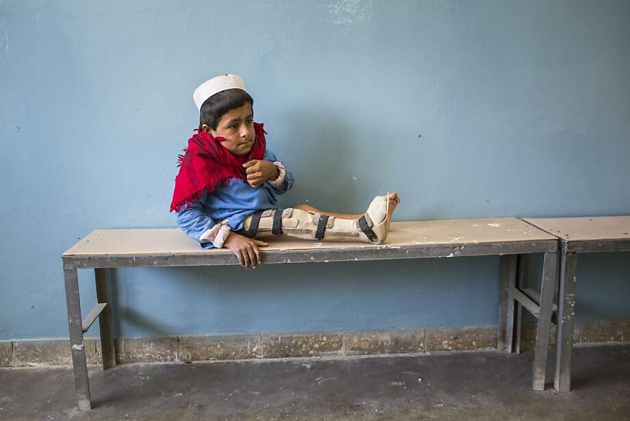 Bismillah Gul, 12, suffering from poliomyelitis waits for his father Masta Gul, after having traveled from Khost province to get treatment at the International Committee of the Red Cross (ICRC) orthopedic center on November 19, 2012 in Kabul, Afghanistan.  Photo: Daniel Berehulak, Getty Images