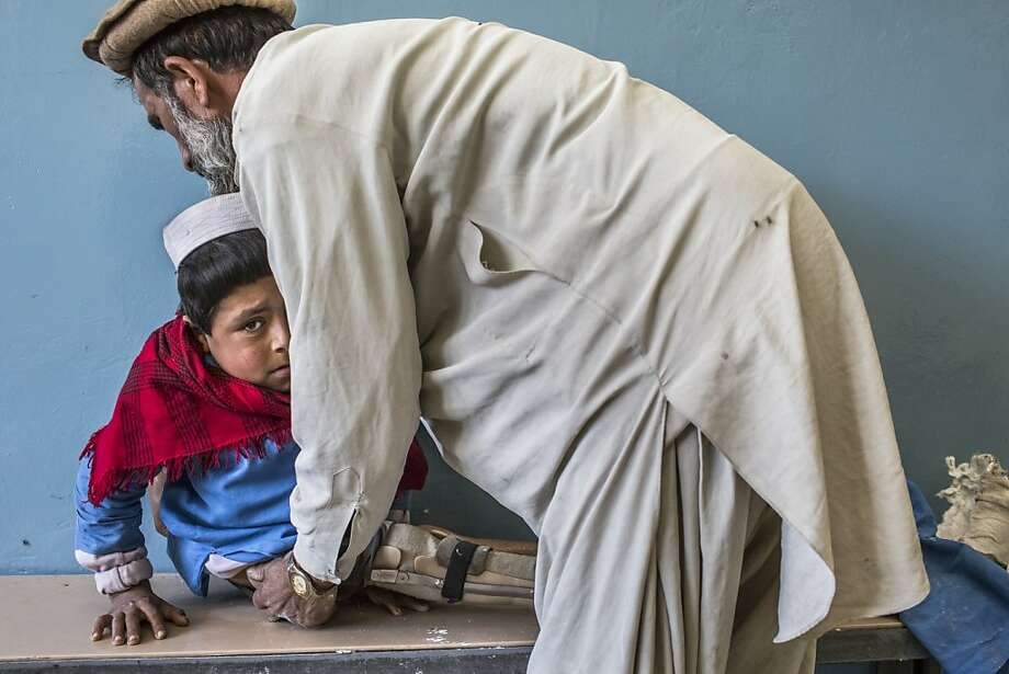 Bismillah Gul, 12, suffering from poliomyelitis is helped by his father Masta Gul, after having traveled from Khost province to get treatment at the International Committee of the Red Cross (ICRC) orthopedic center on November 19, 2012 in Kabul, Afghanistan. Photo: Daniel Berehulak, Getty Images