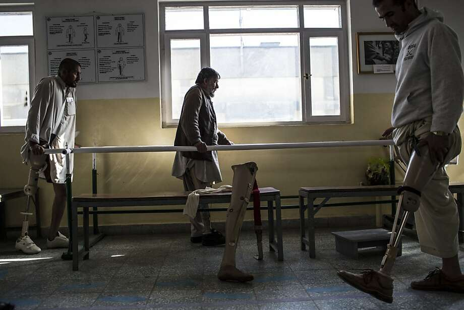 Ehsamullah, 30, (left) who lost his leg after being shot with an AK-47 and Hassibullah, 30, (right) who lost his after stepping on a mine, practice walking with their prosthetic limbs at the International Committee of the Red Cross (ICRC), orthopedic center on November 20, 2012 in Kabul, Afghanistan. Photo: Daniel Berehulak, Getty Images