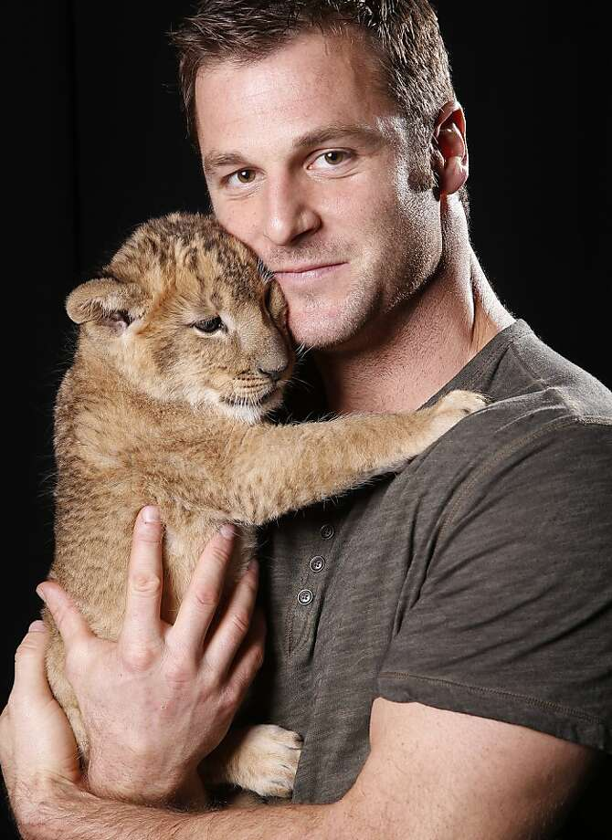 "Careful, Dave, or he'll nuzzle you to death: In New York, Dave Salmoni, Canadian large predator expert and star of Animal Planet's ""Frontier Earth,"" wrestles a ferocious lion into submission. Photo: Carlo Allegri, Associated Press"