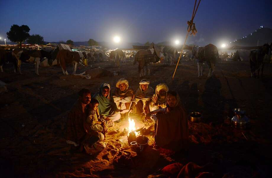 Tales of the hump merchants:Camel traders sit around a fire telling war stories into the wee hours outside Pushkar, India, site of one of the world's largest camel and livestock fairs. Photo: Roberto Schmidt, AFP/Getty Images