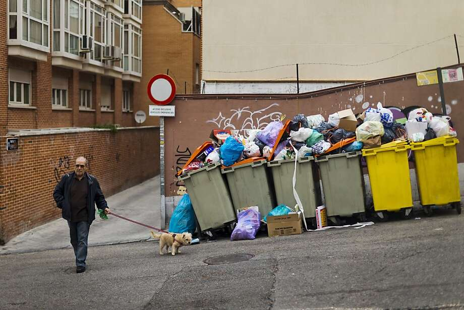 But it stinks so good! A man pulls his dog away from overflowing garbage bins in Madrid. City trash collectors went on strike in an effort to avoid layoffs and pay cuts amid the country's second recession in three years. Photo: Daniel Ochoa De Olza, Associated Press