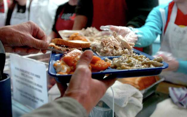A client accepts a free Christmas Dinner from the Catholic Charities of Southeast Texas at the Hospitality Center in Port Arthur, Saturday, December 24,  2011. Tammy McKinley/The Enterprise Photo: TAMMY MCKINLEY
