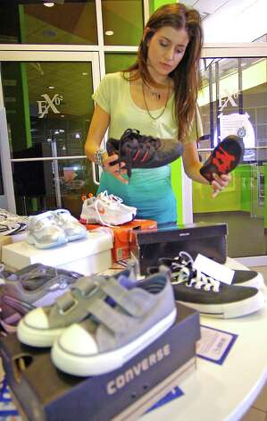 Membership Director Lindsay Briggs arranges some of the donated new shoes on a table at the front of the facility on Phelan Blvd. Exygon is hosting a shoe drive through Buckner Children and Family Services until Saturday. They're asking for new athletic children's shoes to donate to the charity, Shoes for Orphan Souls. There is a table set up outside each location to receive donations. Dave Ryan/The Enterprise Photo: Dave Ryan