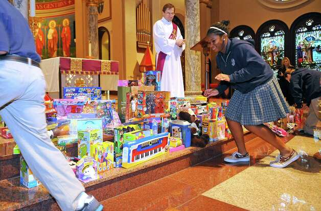 All the students at St. Anthony Cathedral Basilica School donated new toys to the Empty Stocking Fund Tuesday morning. The students brought all the toys to the Basilica from the school where they were placed on the alter.  Deacon Keith Fontenot, waits to bless them with Holy Water before they were to be picked up by the EJ Christmas Bureau volunteers. It was in recognition of the Feast of St. Nicholas which is celebrated on December 6th.    Dave Ryan/The Enterprise Photo: Dave Ryan