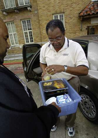 At his second to the last stop on his route, the old downtown Beaumont Y, Ed Moore, right, meets with maintenance employee Steven LeBlanc, and drops off four meals which LeBlanc will hand deliver to residents.   Moore, a former Jefferson County commissioner, has been delivering Meals on Wheels once a week since he retired back in August of 2001.  Dave Ryan/The Enterprise Photo: Dave Ryan / Beaumont