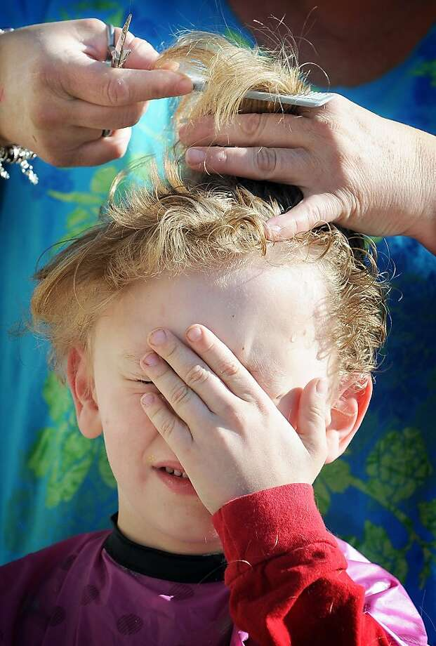 Tell me when it's over:Five-year-old Tyler Norris can't bear to look as his flowing locks are shorn outdoors in Salina, Kan. His grandmother likes it short, he says. Photo: Tom Dorsey, Associated Press