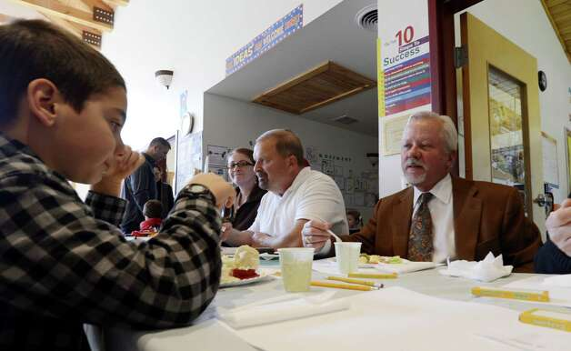 Saratoga Springs Mayor Scott Johnson, right, enjoys his turkey dinner at the Saratoga Independent School's Thanksgiving Feast at the school in Saratoga Springs, N.Y Nov 21, 2012.    (Skip Dickstein/Times Union) Photo: SKIP DICKSTEIN / 00020167A