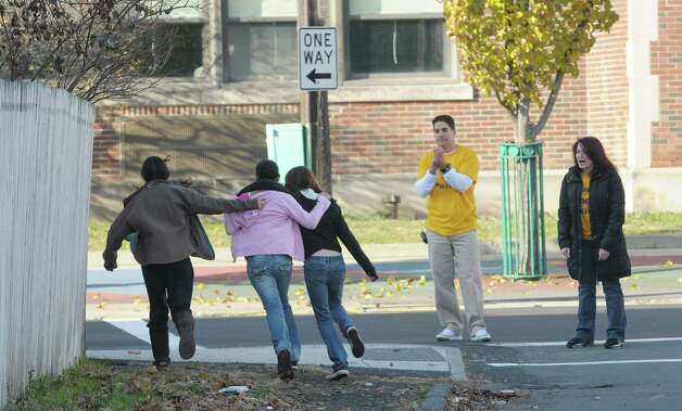 Students run up Harrison Street as Principal Brian Dunn, center, and English teacher Antoinette Costa, right, cheer them on  as seventh and eighth graders at Doyle Middle School took part in the Doyle Dash, a 3/4 of a mile run/walk on the streets near the school    (Paul Buckowski / Times Union) Photo: Paul Buckowski / 00020224A