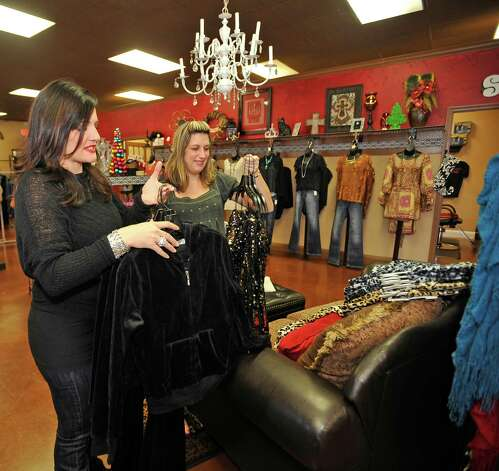 "April LeBlanc, left, who is the owner of Serenity Boutique and Salon in Silsbee, and Amanda Cravey, right, bring out more merchandise to hang on the racks for tomorrow's sale. LeBlanc will be opening her doors on Thanksgiving Day at 6 p.m. for early retail shoppers. She will be competing with ""big box"" retailers despite her starting the fad in 2010 when she first opened her doors as a new business. She is afraid that the new ""big"" store trend could hurt her by opening their doors on Thanksgiving, a holiday reserved for family, as well.   Dave Ryan/The Enterprise"