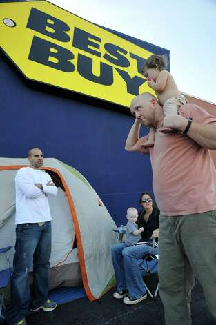 Seasoned Black Friday shoppers like Jared Gilthorpe, right, seen here carrying his daughter Charlie around on his shoulders because she was barefoot, and his friend Marcus Paterno, left, are already lined up outside of Best Buy with a tent in Beaumont, hoping to scoop up deals on electronics. Gilthorpe's wife Brooke, middle, with Boone on her lap,  and Charlie, top right, were visiting for the afternoon, but had no plans to stay through the night. Dave Ryan/The Enterprise Photo: Dave Ryan