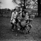 Young people and turkeys are pictured on a poultry farm in Hertfordshire, U.K., on Nov. 23, 1929.