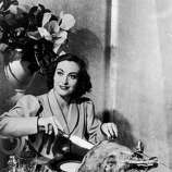 Here's actress Joan Crawford (1908 - 1977) carving a Thanksgiving turkey for a publicity shot, circa 1930.