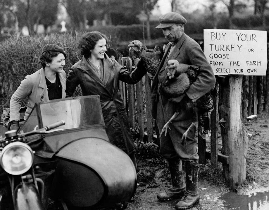 Two women passing a country farm near Tewkesbury, Gloucestershire,  admire turkeys offered for sale on Dec. 20, 1936. Photo: Fox Photos, Getty Images / Hulton Archive