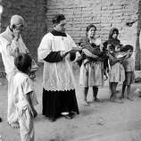 A priest blesses turkeys and other animals at the Blessing of San Antonio de Abad, patron saint of animals, circa 1952.