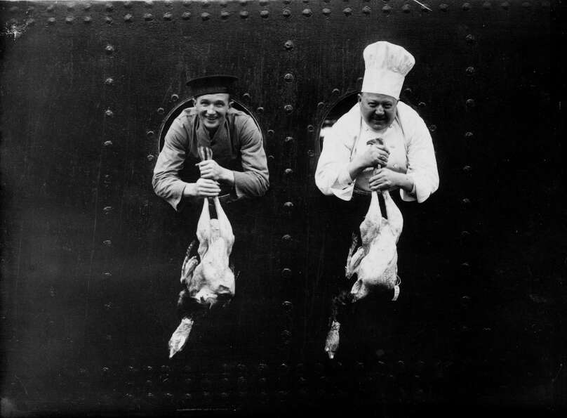 The ship's chef and a kitchen worker display Christmas turkeys through portholes on the P&O liner