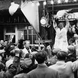 An auctioneer holds up a turkey for auction on Dec. 22, 1961 at London's Smithfield market.