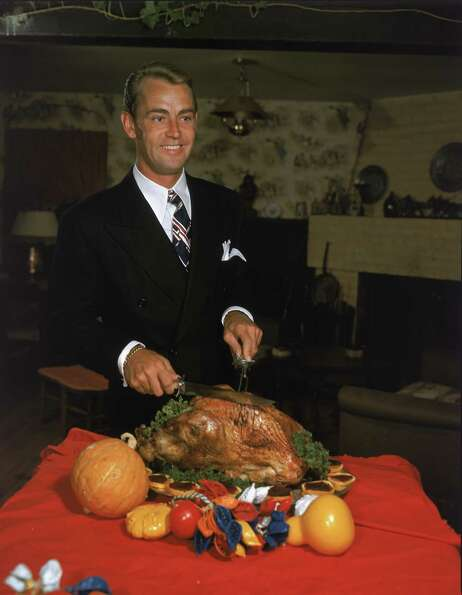 Actor Alan Ladd (1913 - 1964) carves a Thanksgiving turkey in a promotional portrait from the 1950s.