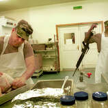 First Sergeant Victor Franco, left, of Puerto Rico, volunteers his time and his father's recipe to prepare turkeys which will be served to soldiers for Thanksgiving dinner at Camp Bondsteel in Kosovo, Nov. 22, 2000.
