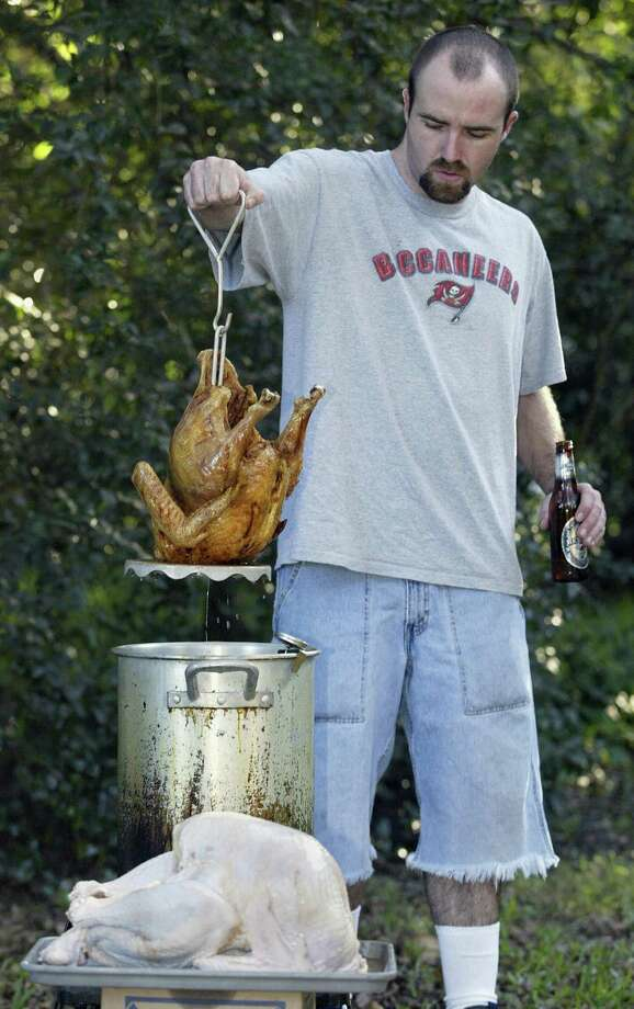 One easy piece of advice is to make sure you really know what you're doing if you want to deep-fry a turkey. Here, John Wojtasik removes a turkey from hot peanut oil on Nov. 27, 2003, at Markham Park in Fort Lauderdale, Fla. Photo: ROBERT SULLIVAN, AFP/Getty Images / 2003 AFP