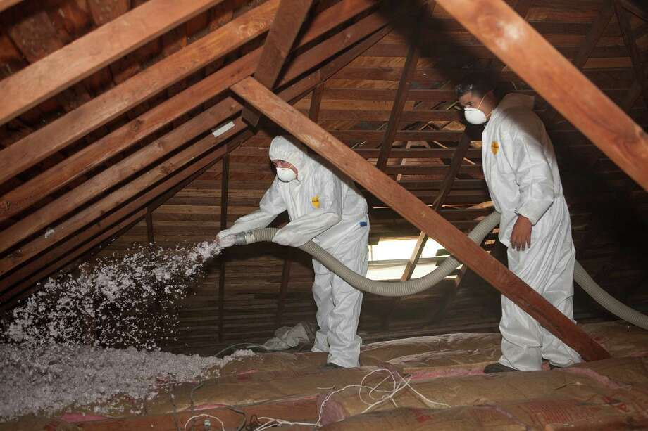CPS Energy contractors add cellulose insulation in an attic that already has fiberglass insulation. The additional insulation will help keep heat from escaping through the attic during cold weather. Photo: Courtesy Photo / Photo courtesy of CPS Energy