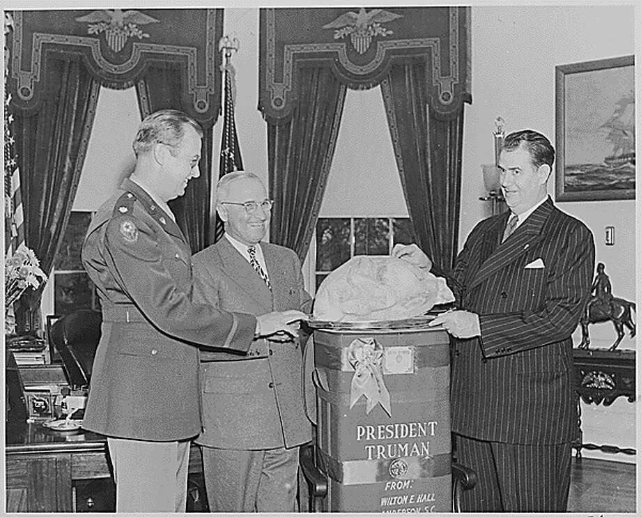 Sen. Olin Johnston of South Carolina, left, presents President Harry Truman with a turkey from Wilton E. Hall of Anderson, S.C., as Col. Lewis Jackson observes on Nov. 25, 1946. Photo: Harry S. Truman Library/National Archives And Records Administration