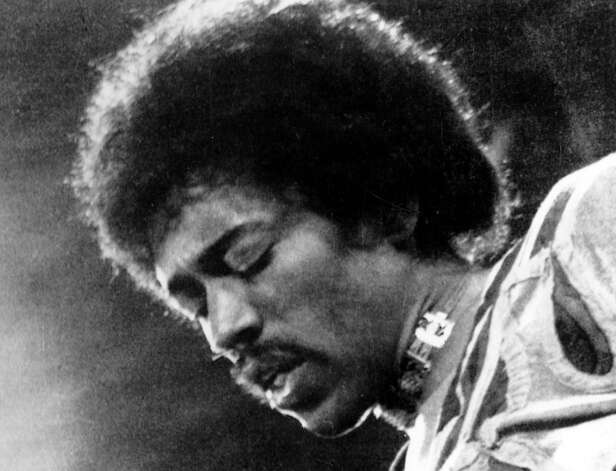 "FILE- In this 1970 file photo, Jimi Hendrix performs on the Isle of Wight in England. A new Jimi Hendrix album is coming March 5. The musician's website says ""People, Hell and Angels"" contains 12 previously unreleased tracks recorded in 1968 and '69. Rolling Stone revealed the album cover on its website Wednesday, Nov. 21, 2012.(AP Photo/file)"