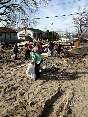 Julia and Ashton Monteiro, Cameron and Gavin O'Carroll, and Shyam and Faiz Rahim, all of Greenwich, help clean up trash in Breezy Point, N.Y., Sunday, Nov. 18, 2012, to help the residents of the Queens neighborhood in the ongoing cleanup in the wake of Hurricane Sandy. Photo: Contributed Photo