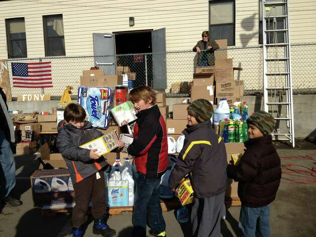 From left, Gavin O'Carroll, Ashton Monteiro, and Shyam and Faiz Rahim, all of Greenwich, help organize supplies their families brought to Breezy Point, N.Y., Sunday, Nov. 18, 2012, to help the residents of the Queens neighborhood in the ongoing cleanup in the wake of Hurricane Sandy. Photo: Contributed Photo