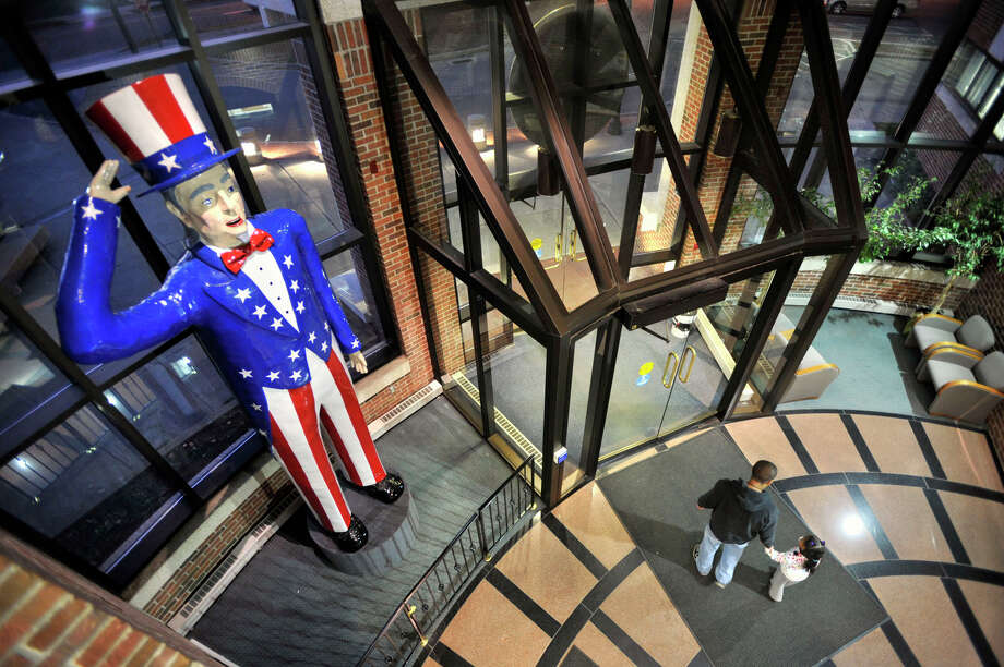 People walk by a statue of Uncle Sam in the atrium of Danbury City Hall on Wednesday, Nov. 21, 2012. Charlie Payne, a city firefighter, is lending the city the larger-than-life statue that once stood at the southern entrance to the Danbury Fair. Photo: Jason Rearick / The News-Times
