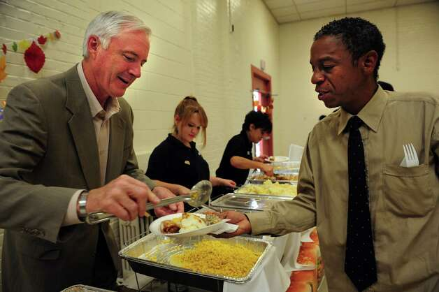 Mayor Bill Finch serves dinner to Craig Faulk during the Marina Village Thanksgiving Dinner Wednesday, Nov. 21, 2012 at the Marina Village Community Room. Photo: Autumn Driscoll / Connecticut Post
