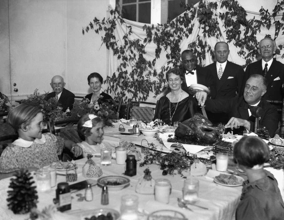 President Franklin D. Roosevelt carves the turkey during the annual Thanksgiving dinner for polio patients at Warm Springs, Ga., with first lady Eleanor Roosevelt smiling beside him, Dec. 1, 1933.  (AP) Photo: ASSOCIATED PRESS / AP1933